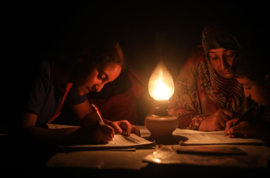 A woman helps children study under candle light during a power cut in Khan Yunis, Gaza on August 18, 2020. After Israel tightened the blockade in Gaza Strip, the only power plant in the area stopped production affecting the life especially the health sector. Photo by Mustafa Hassona. Anadolu Agency.